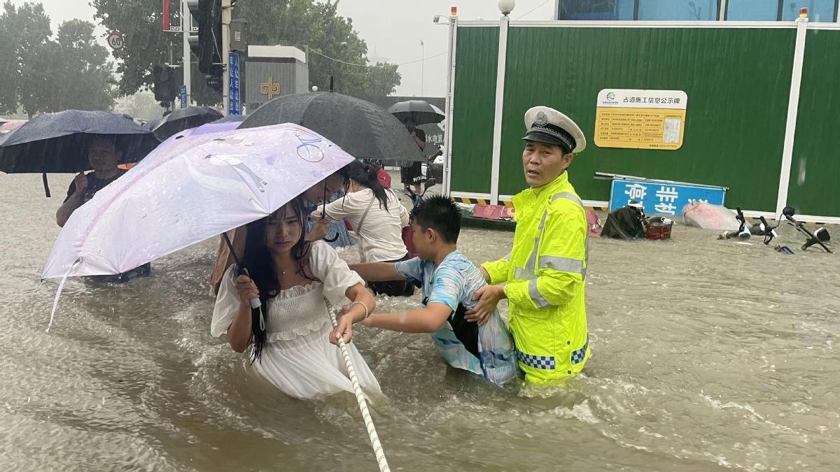 Police Help People Cross Flooded Roads in C China's Zhengzhou