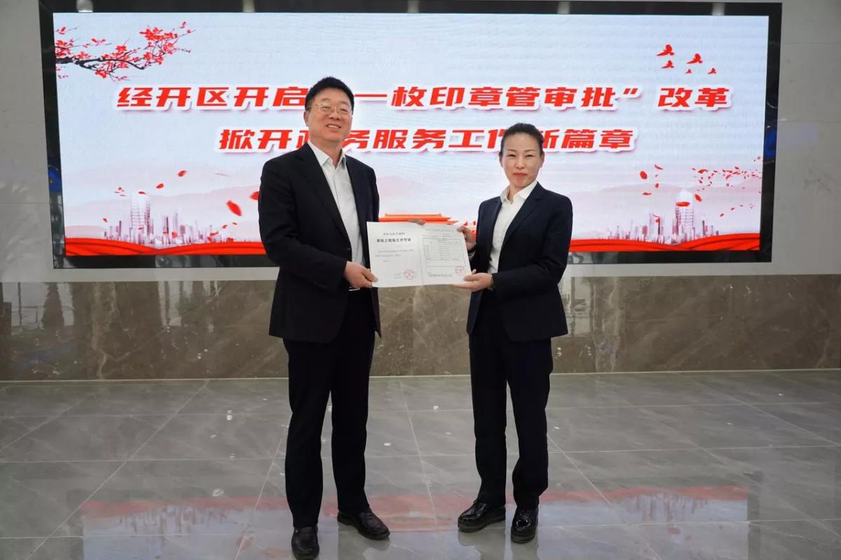 经开区党工委书记刘思江(左)向公司负责人发放许可证 王新林 摄